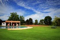 Une vue du jardin avec la piscine et le terrain de tennis